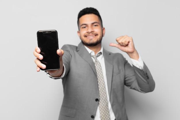 ヒスパニック系のビジネスマンの幸せな表情と電話を持っている