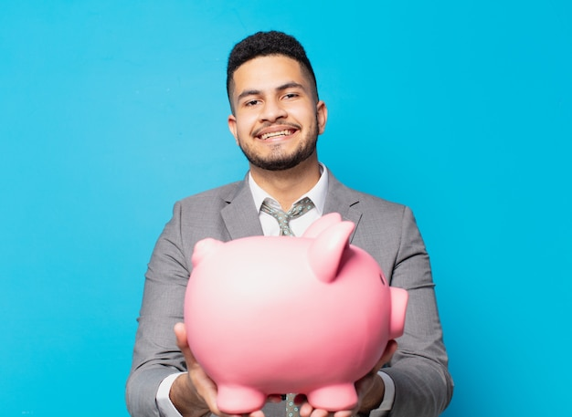 Hispanic businessman happy expression and holding a piggy bank