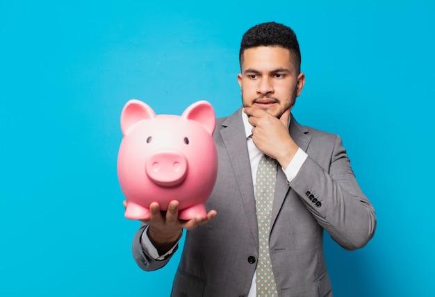 ヒスパニック系のビジネスマンは表情を怖がり、貯金箱を持っています