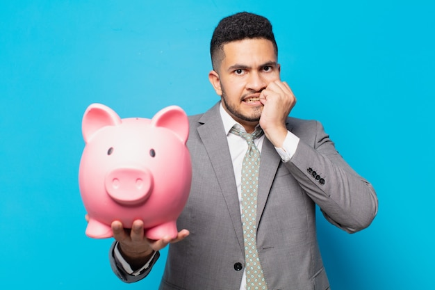 Hispanic businessman scared expression and holding a piggy bank