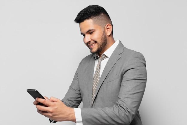 表現を考え、電話を持っているヒスパニックの実業家