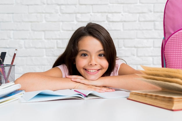 Hispanic cheerful girl sitting at desk