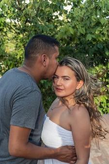 公園でヒスパニック系のカップル。彼氏がガールフレンドにキスします。