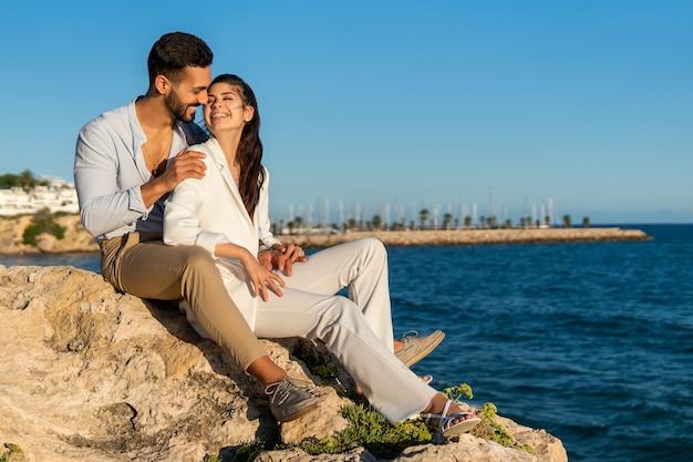 Hispanic couple in love on rocks at seaside