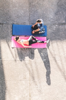 Hispanic couple stretching on yoga mats