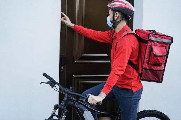 ドアベルを鳴らしている電動自転車を持つヒスパニックの配達人-顔に焦点を当てる