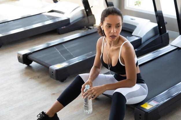 Hispanic female having a break from the workout