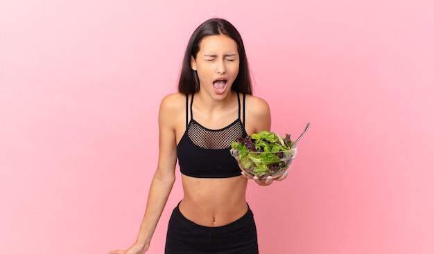 積極的に叫び、非常に怒っているように見え、サラダを持っているヒスパニックのフィットネス女性