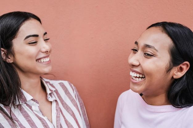 야외에서 함께 웃고 즐기는 히스패닉 친구들 - 오른쪽 여자 얼굴에 집중