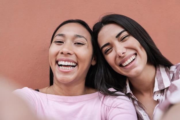 街の屋外で携帯電話で自分撮りを楽しんでいるヒスパニック系の友人-顔に焦点を当てる