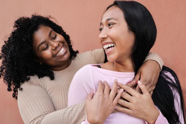 街で屋外で一緒に楽しんでいるヒスパニック系の友人-右の女の子の顔に主な焦点