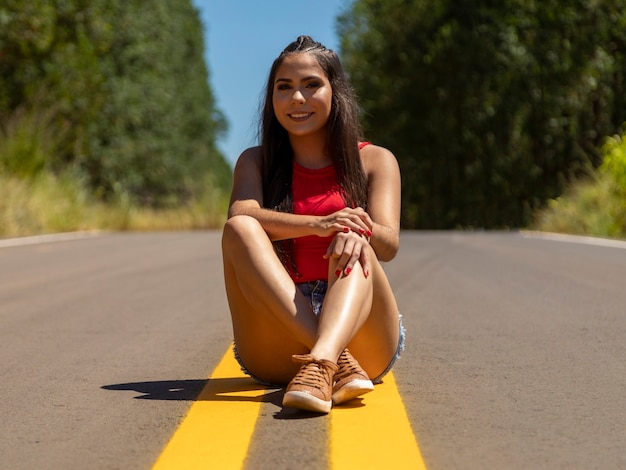 高速道路の真ん中にヒスパニック系の女の子、背景に自然。