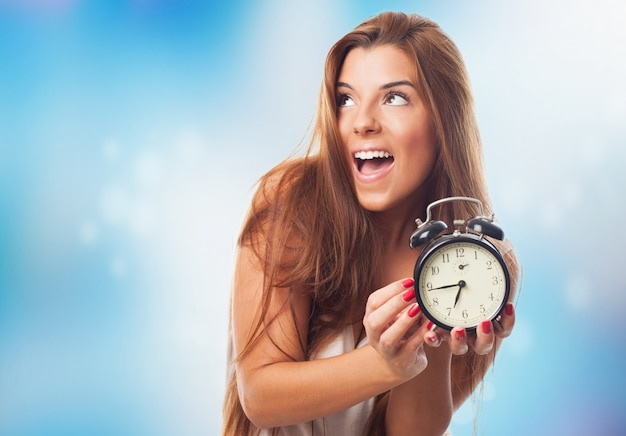 Hispanic girl with alarm clock