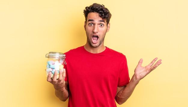ヒスパニック系のハンサムな男は、信じられないほどの驚きに驚き、ショックを受け、驚きました。キャンディーのコンセプト