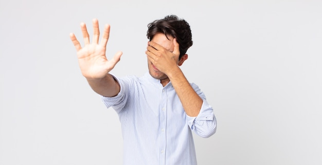 Hispanic handsome man covering face with hand and putting other hand up front to stop camera, refusing photos or pictures