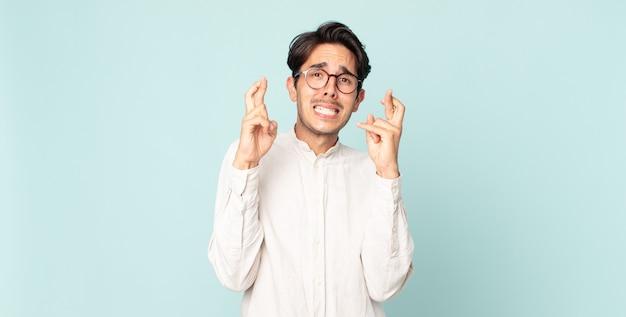 히스패닉 잘생긴 남자가 걱정스럽게 손가락을 교차하고 걱정스러운 표정으로 행운을 바라고 있습니다