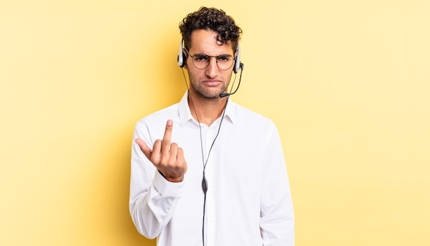 Hispanic handsome man feeling angry, annoyed, rebellious and aggressive. telemarketer concept