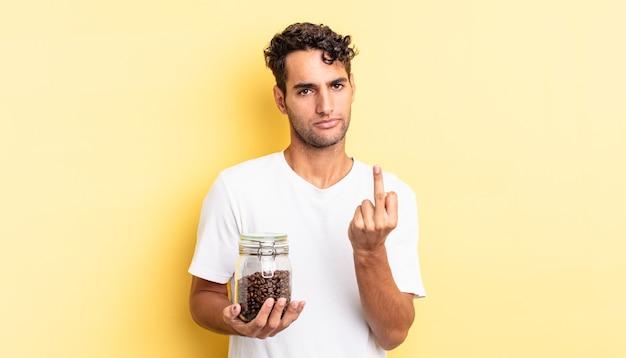 Латиноамериканский красавец чувствует себя злым, раздраженным, мятежным и агрессивным. бутылка кофе в зернах