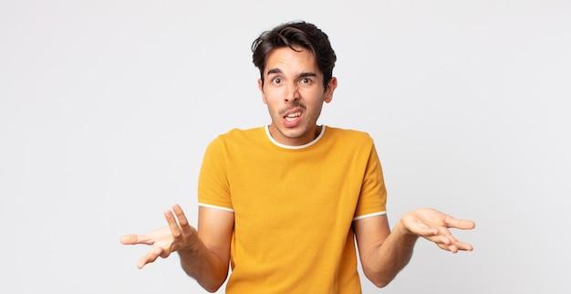 ヒスパニック系のハンサムな男は無知で混乱していると感じ、どの選択肢やオプションを選ぶべきかわからない、疑問に思っています