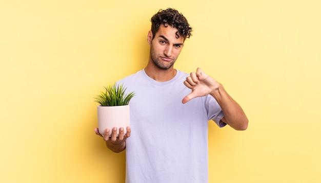 Испаноязычный красавец чувствует крест, показывает палец вниз. концепция декоративного растения