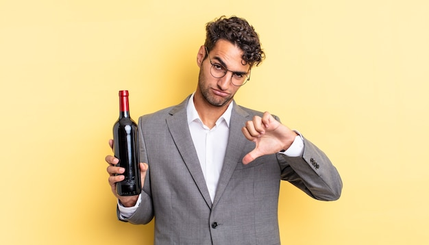 Испаноязычный красавец чувствует крест, показывает палец вниз. концепция бутылки вина