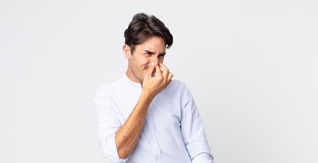 ヒスパニック系のハンサムな男は嫌悪感を感じ、悪臭や不快な悪臭を避けるために鼻を保持します