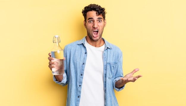 非常にショックを受けて驚いたヒスパニック系のハンサムな男。ウォーターボトルのコンセプト