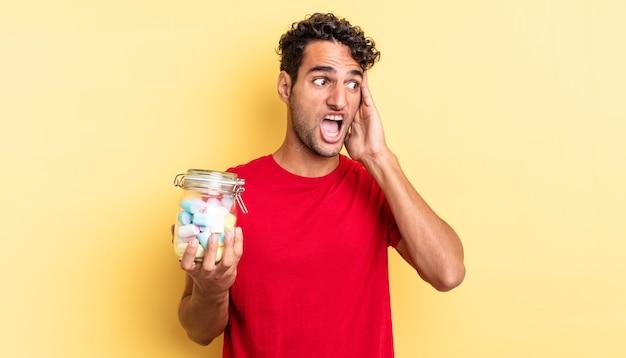 幸せ、興奮、驚きを感じているヒスパニックのハンサムな男。キャンディーのコンセプト