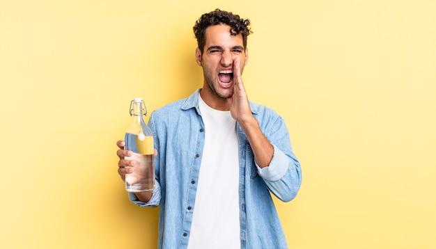 ヒスパニック系のハンサムな男は、口の横に手を置いて大きな叫び声をあげて、幸せを感じています。ウォーターボトルのコンセプト