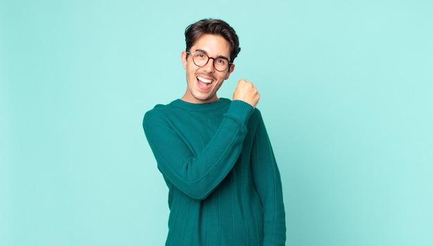 ヒスパニック系のハンサムな男性は、挑戦に直面したり、良い結果を祝ったりするときに、幸せで、前向きで、成功し、やる気を感じます