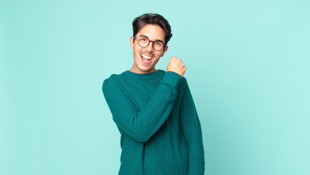 Hispanic handsome man feeling happy, positive and successful, motivated when facing a challenge or celebrating good results