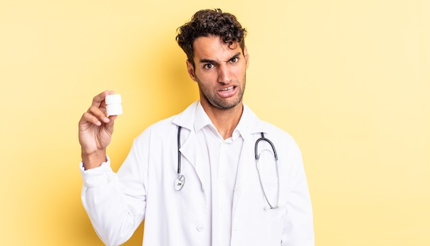 困惑と混乱を感じているヒスパニックのハンサムな男。医師のボトルの丸薬の概念