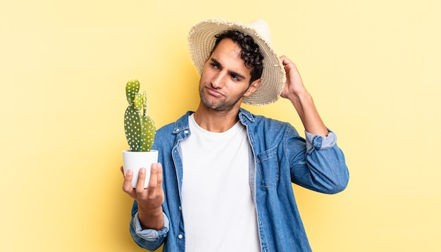 Hispanic handsome man feeling puzzled and confused, scratching head farmer and cactus concept