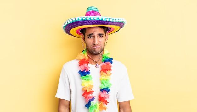 ヒスパニック系のハンサムな男は、不幸な表情と泣き悲しみと泣き言を感じています。メキシコのパーティーのコンセプト