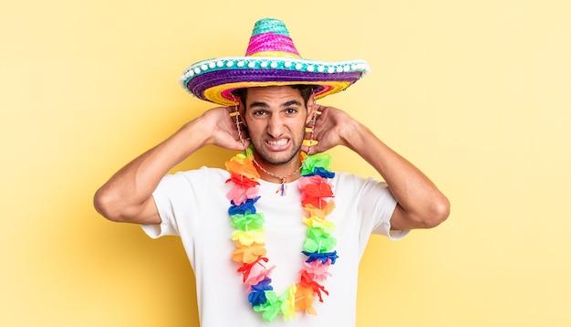 ヒスパニック系のハンサムな男性は、頭に手を置いて、ストレス、不安、または恐怖を感じています。メキシコのパーティーのコンセプト