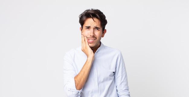頬を持ち、痛みを伴う歯痛に苦しんでいるヒスパニック系のハンサムな男、気分が悪く、惨めで不幸で、歯科医を探しています