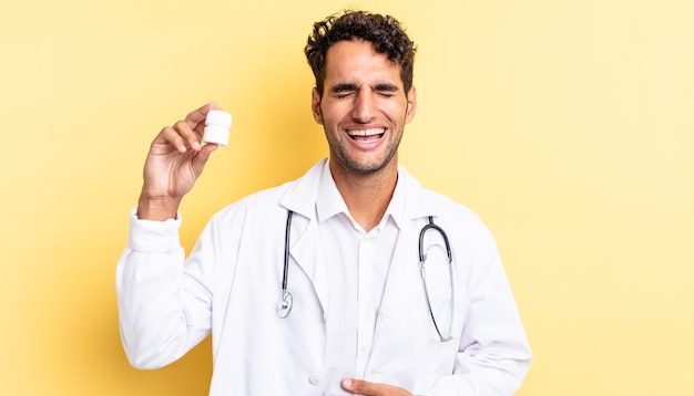 Hispanic handsome man laughing out loud at some hilarious joke. physician bottle pills concept