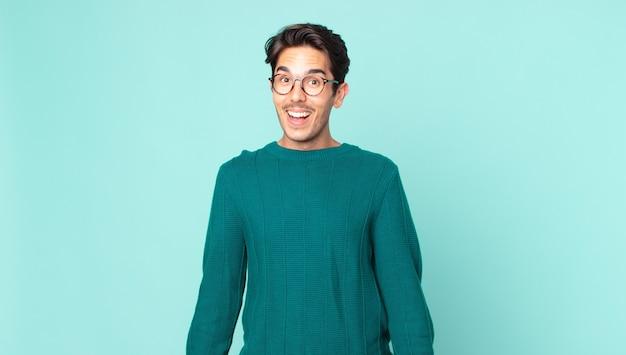 ヒスパニック系のハンサムな男は、魅了され、ショックを受けた表情で興奮し、幸せで嬉しい驚きに見えます