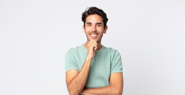 ヒスパニック系のハンサムな男は、幸せそうに見えて、あごに手を当てて笑って、疑問に思ったり、質問したり、オプションを比較したりします