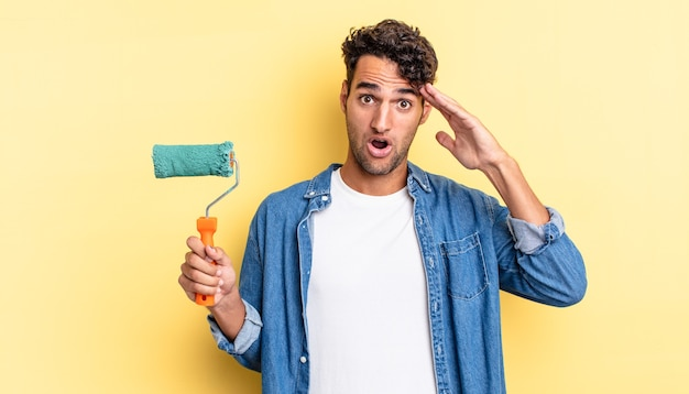 Hispanic handsome man looking happy, astonished and surprised. roller paint concept