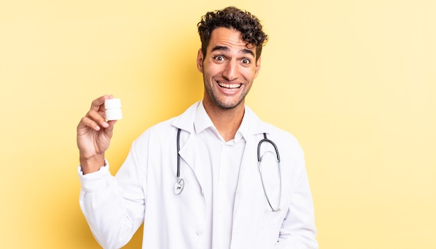 Hispanic handsome man looking happy and pleasantly surprised. physician bottle pills concept