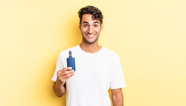 Hispanic handsome man looking happy and pleasantly surprised. vaporizer concept