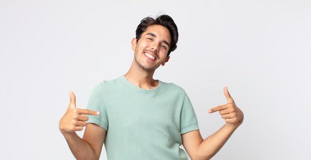 誇らしげに、傲慢で、幸せで、驚き、満足している、自己を指している、勝者のように感じているヒスパニック系のハンサムな男