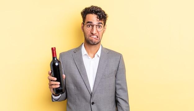 困惑して混乱しているように見えるヒスパニック系のハンサムな男。ワインボトルのコンセプト