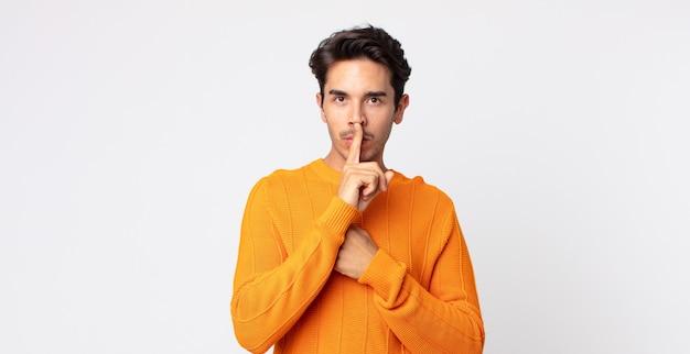 真面目そうに見えるヒスパニック系のハンサムな男が、秘密を守りながら、沈黙または静寂を要求する唇に指を押し付けて交差する