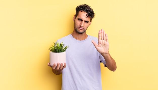 Испаноязычный красивый мужчина выглядит серьезным, показывая открытую ладонь, делая стоп-жест. концепция декоративного растения