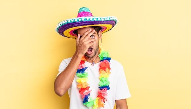 ヒスパニック系のハンサムな男は、手で顔を覆って、ショックを受けたり、怖がったり、恐怖を感じたりします。メキシコのパーティーのコンセプト