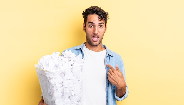 Hispanic handsome man looking shocked and surprised with mouth wide open, pointing to self. paper balls trash concept
