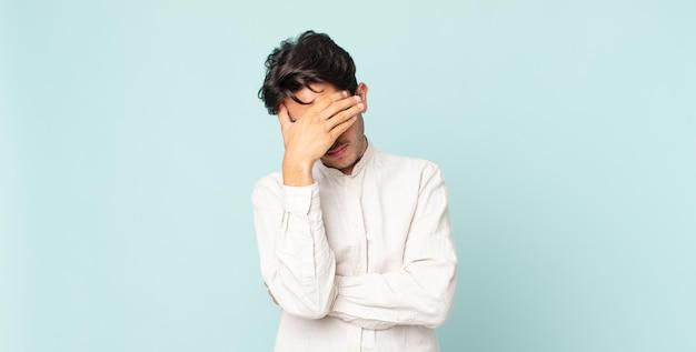 ストレス、恥ずかしがり屋、または動揺して、頭痛で顔を覆っているヒスパニック系のハンサムな男