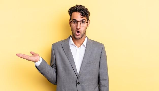 ヒスパニック系のハンサムな男は、物を持って顎を落とし、驚いてショックを受けました。ビジネスコンセプト